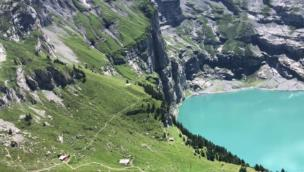 Lad eats smoked ham and cheese near beautiful mountains and lake in Oeschinensee, Switzerland collection item