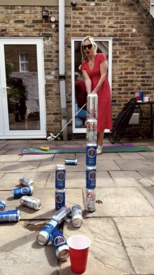 Woman chips balls over beer can tower collection item