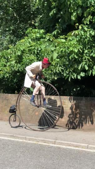 Lad rides a pennyfarthing down the street collection item