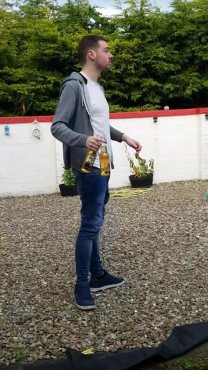 Lad opens beer bottle by kicking other beer bottle collection item