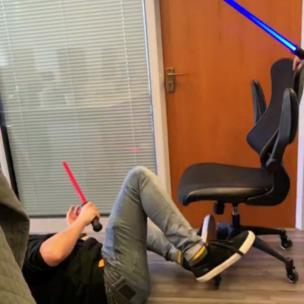 Slo-mo of two lads doing lightsaber jousting on offices chairs collection item