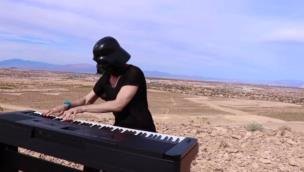 Lad plays the Star Wars Imperial March dressed as Darth Vader in a desert collection item